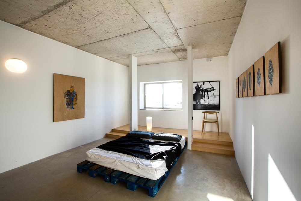 Dormitorio con cama hecha con palets